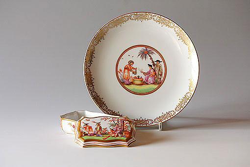 """""""シノワズリー""""は、当時のヨーロッパの人々の東洋への憧憬が投影された中国趣味の美術様式を指します。マイセン シノワズリーは華やかな色彩と繊細で幻想的な描写が特徴です。大変小さなモチーフとして描かれます。""""ヘロルト""""は1700年代にマイセンで活躍した絵付師で、マイセン史に残る多くの図案を世に送り出しました。"""